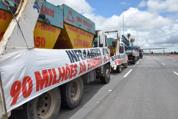 Empresas levaram caminhões e faixas para a porta de acesso ao aeroporto para cobrar dívida. (Foto: Emanuel Amaral)